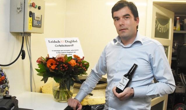 Leon de Mooij met het winnende flesje bier.
