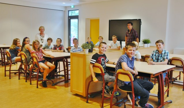 Groep 8 van de Regenboog in de fonkelnieuwe aula. Linksachteraan staat locatieleider Carla Kerner.