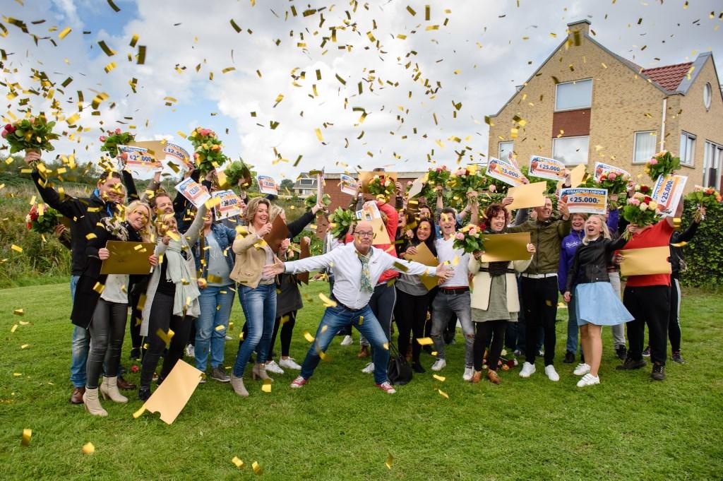 Winnaars uit Katwijk worden verrast door Postcode Loterij ambassadeur Gaston Starreveld met de PostcodeStraatprijs-cheque.