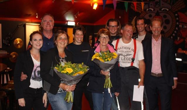 De vrouwen van de jubilerende brandweermannen krijgen de bloemen in handen. | Foto: Annemiek Cornelissen