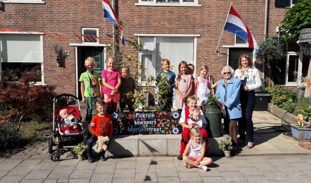 De kinderen uit de Marijkestraat onthullen de pluktuin, samen met burgemeester Breuer en mevrouw Smit (92).   Foto: MV