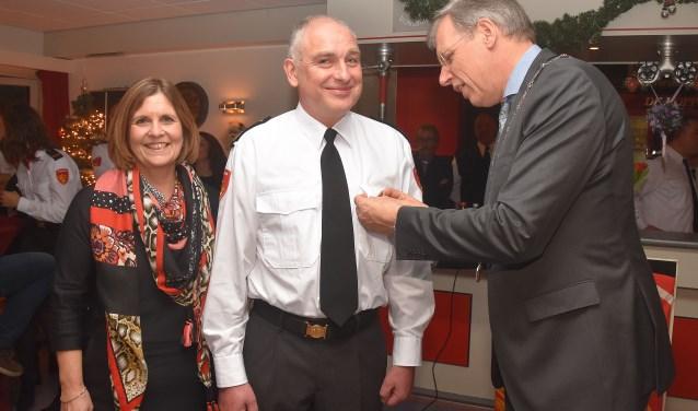 Burgemeester Visser speldt de koninklijke onderscheiding op bij André Jonker.