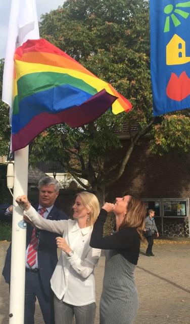 Wethouders Kees van der Zwet, Jeanet van der Laan en Jolanda Langeveld hijsen de blanco en de regenboogvlag.