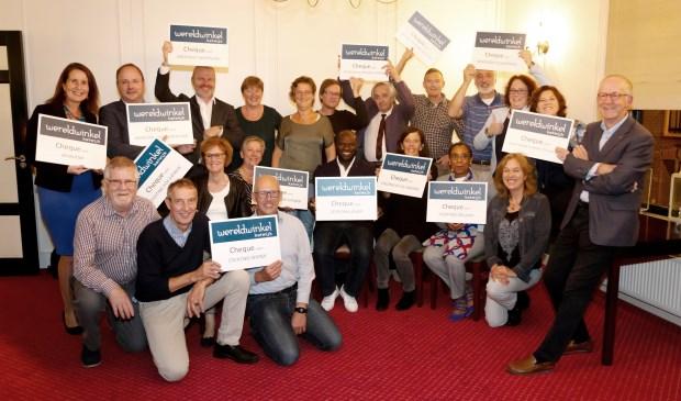 Voorzitter Rob van Vreedendaal (rechts) heeft zojuist aan alle 13 organisaties hun cheque overhandigd en die zijn er blij mee.