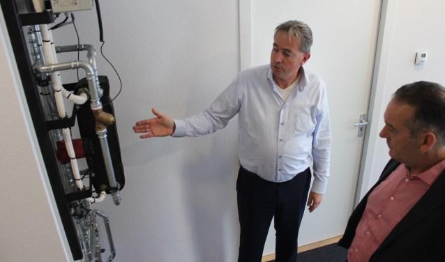 Wethouder Rob ten Boden bekijkt met eigenaar Homan van het bedrijf Fore de opmerkelijke energiezuinige installatie voor de regeling van warmte.   Foto: NK