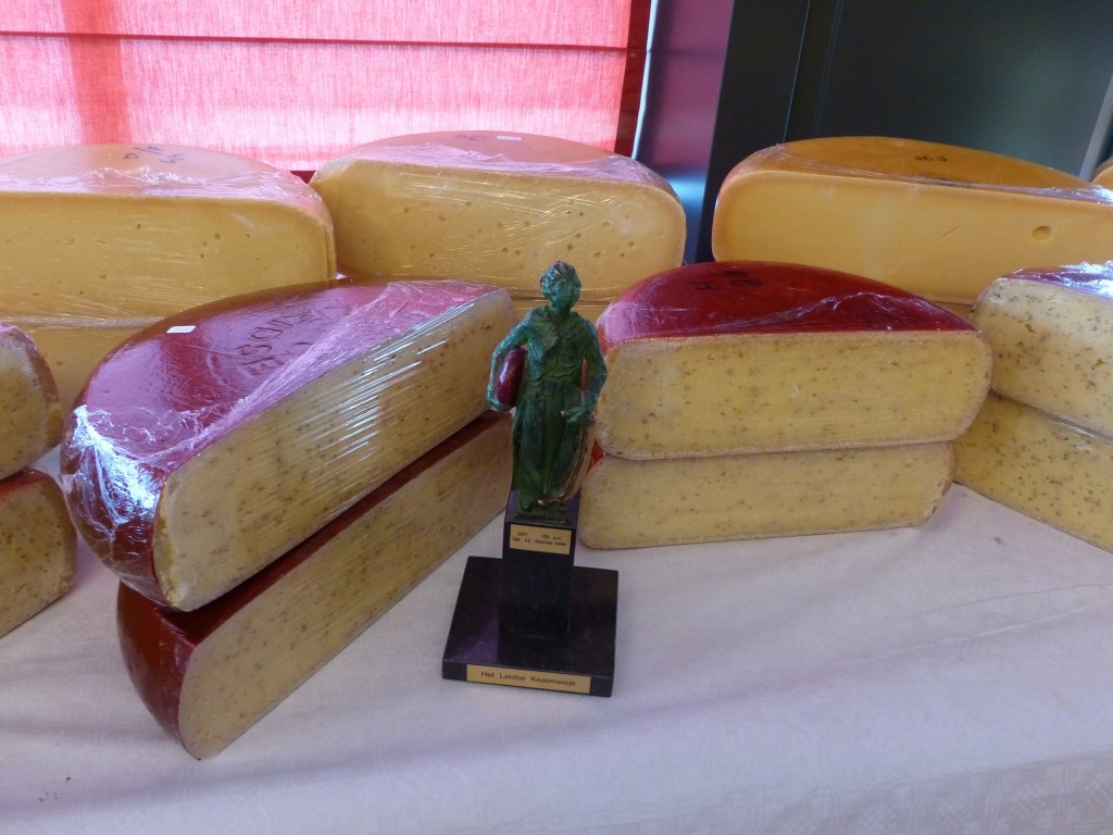 Wisselbeker het Leids kaasmeisje tussen de gekeurde kazen.  © uitgeverij Verhagen