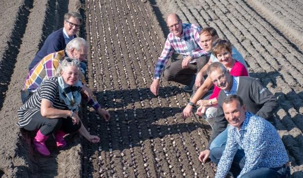 Het bestuur plant de hyacintenbollen bij VOF J Heemskerk aan de 1e Loosterweg in Hillegom.