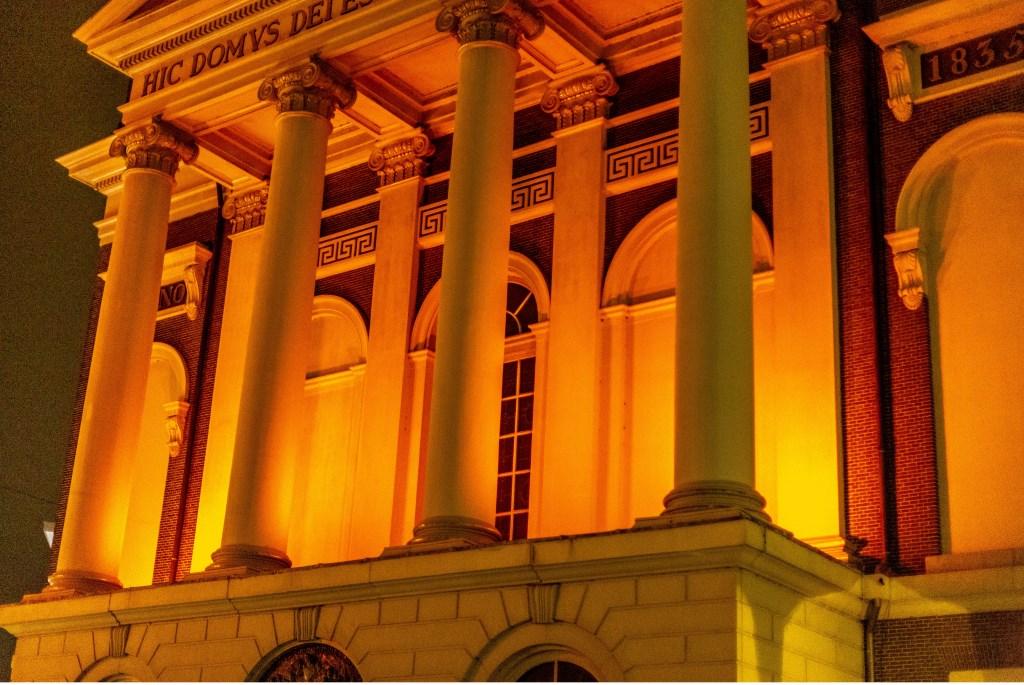 Op de witte gevel van de Hartebrugkerk komt het oranje licht mooi uit.  Foto: Wil van Elk © uitgeverij Verhagen