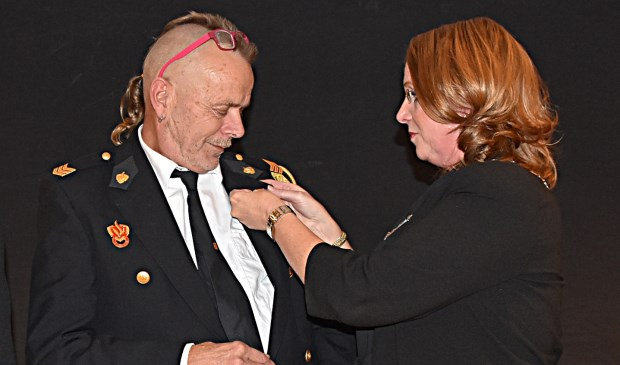 Ron Hoogeboom krijgt de koninklijke onderscheiding opgespeld door burgemeester Carla Breuer.   Foto: Piet van Kampen