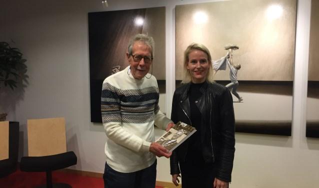 Met trots presenteert Arie zijn vierde kleine kroniek van Lisse aan wethouder Jeanet van der Laan.