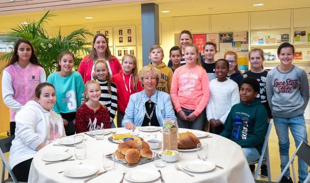 Groep 8 van 't Bolwerk en burgemeester Driessen vlak voor ze aan hun gezonde ontbijt beginnen.