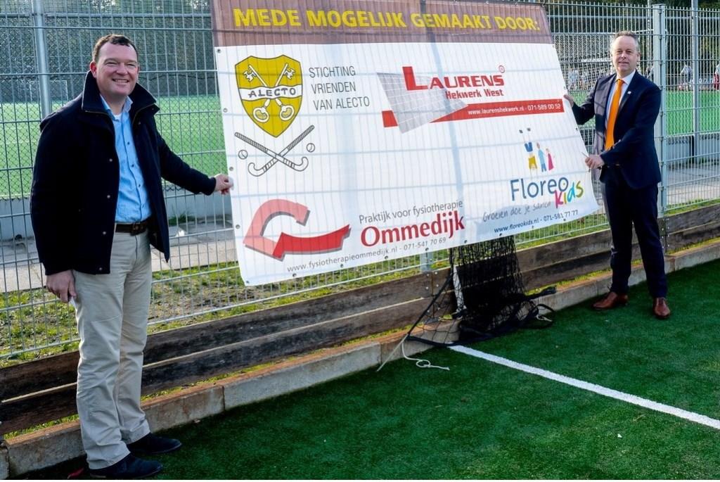 Alecto-voorzitter Bart Kerkmeer (links) en wethouder Willem Joosten onthullen een banner met de namen van de sponsoren van het pannaveldje.   Foto: Johan Kranenburg © uitgeverij Verhagen