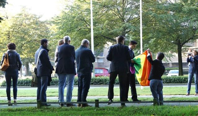 Raadsleden en COC-leden bij het hijsen van de regenboogvlag in de mast tegenover het gemeentehuis.