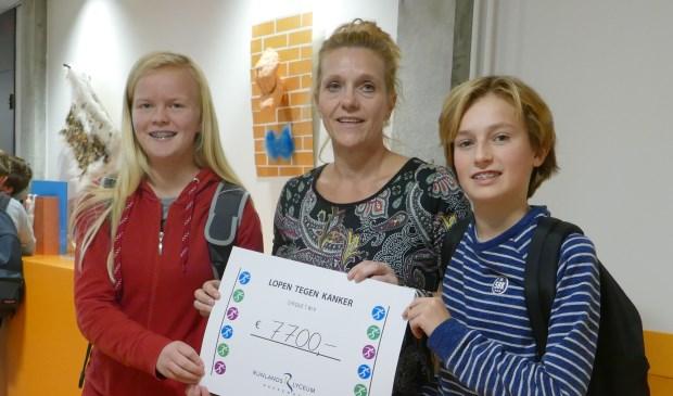 Jazahra Vogel en Storm Ligtvoet overhandigen Corina van Diest van 'Lopen tegen Kanker' symbolisch de cheque met het bij elkaar gelopen bedrag. | Foto: pr.