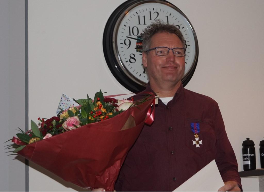 Christian van der Klauw met bloemen en oorkonde.