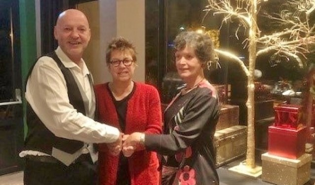 Voorzitter van het district Renée Lucas, midden, drukt de hand van voorzitter Frans van Rijn en secretaris Petra Montagne van de afdeling Duin en Bollenstreek Rode Kruis.