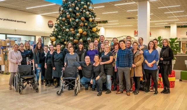 Ook de winkeliers staan achter het plan voor een rolstoeluitleen in Winkelhof. Een groot aantal van hen ging vorige week met Annelies Hoedt (geheel links) en Mariette Meulman (achter rechter rolstoel) op de foto als teken van steun. De beoogde rolstoelen zien er overigens niet zo uit als die op de foto. | Foto: J.P. Kranenburg