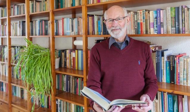 Ton Hetebrij voor de boekenkast vol verhalen. 'Boven staan nog veel meer boeken.' | Foto: Adrie van Duijvenvoorde.