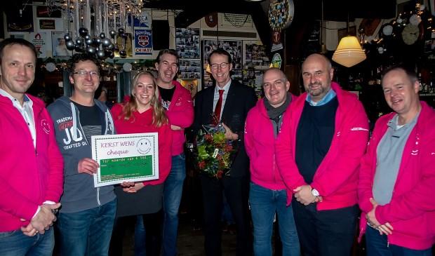 Het bestuur van de Vrienden van het Oude Dorp (in roze vesten) met tweede van rechts voorzitter Fried de Rave samen met Sven Vletter van het PC Hooftcollege (tweede van links) en Vriend van de Vrienden Kees van Haasteren (vierde van rechts).