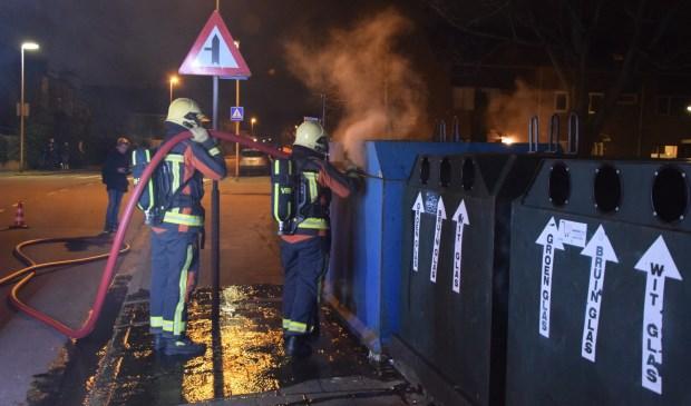 De brandweer maakt korte metten met de fik in de papiercontainer.