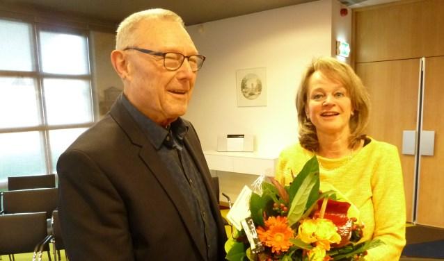 Joop Zwetsloot, de maker van het nieuwe filmpje, krijgt van Lies Spruit een bos bloemen als dank.