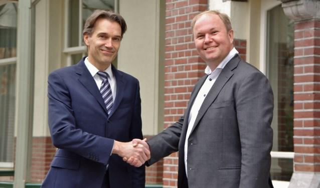 Fractievoorzitter Sven Spaargaren schudt Marcus Rolloos (r) de hand, die met 164 voorkeurstemmen opnieuw een zetel in de gemeenteraad heeft weten te veroveren.   Foto Willemien Timmers