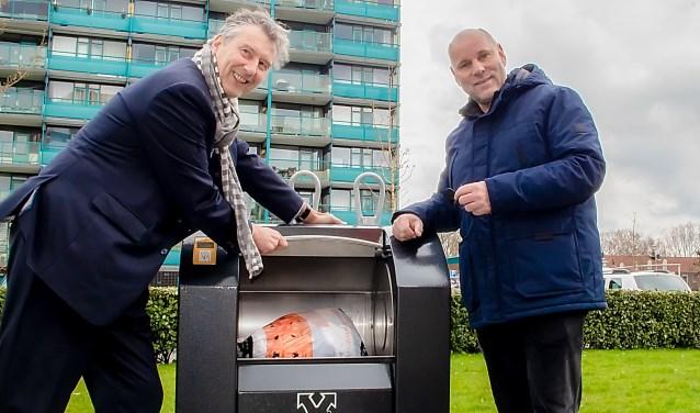Marc Vooges van Sympany (links) en wethouder Olaf McDaniel hebben de textielcontainer met de elektronische sleutel geopend en doneren een zak textiel.