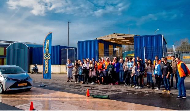 De groep deelnemers en coaches kijken toe hoe wethouder Kees Wassenaar een noodstop maakt op de slipbaan.