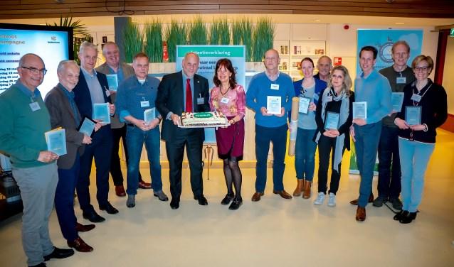 Dertien van de EA's met hun certificaten. Wethouder McDaniel staat al klaar met de taart. Tweede en derde van links staan Patrick Ploeg en Richard Hilhorst, EA's van 't Heerlijk Recht. | Foto: Johan Kranenburg