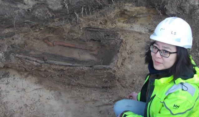 Archeologe Minja Hemminga bij de enige grafkist die de eeuwen in de 'verwoestende' zandgrond heeft getrotseerd. | Foto: Piet de Boer