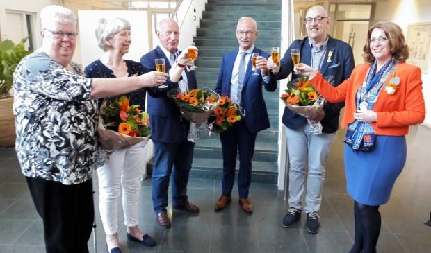 De vijf gedecoreerden, Nel Berg – van Kampen, ElsAlewijnse – de Groot, Hans van Rooijen, TonOostdam en Willem Vogels, heffen het glas met burgemeester Carla Breuer. Rob de Graaff kon door omstandigheden niet aanwezig zijn. | Foto: MV