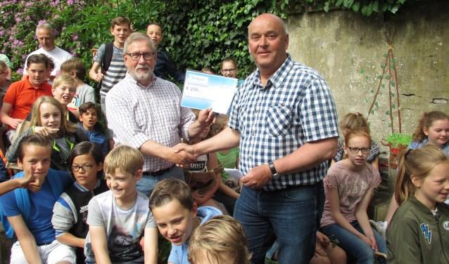 Hans Wilson krijgt de cheque van de Teylinger Prijs vorig jaar overhandigd van jurylid Dion Piket (r). | Foto: pr.