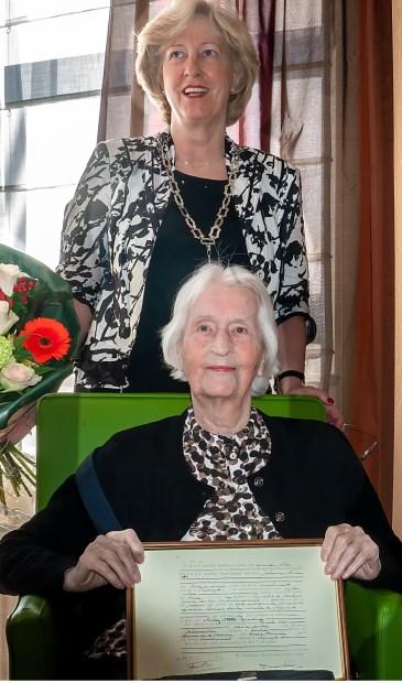 Mevrouw Timmers met haar ingelijste geboortecertificaat. Achter haar staat burgemeester Driessen, die de eeuwelinge namens de gemeente Leiderdorp kwam feliciteren.