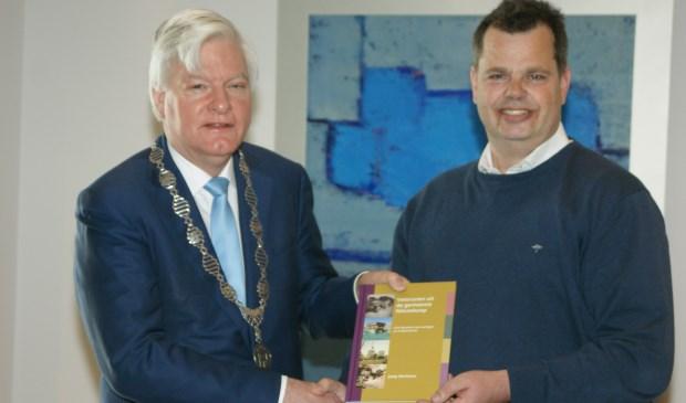 Het eerste exemplaar van het 'Veteranenboek Nieuwkoop' overhandigde Derksen aan burgemeester Buijserd.
