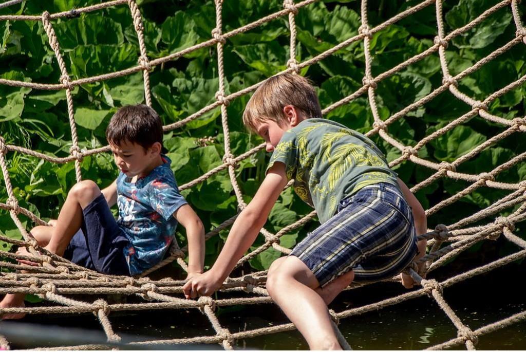 Klimmen in een net dat over het water is gespannen, een activiteit van Scouting Van der Does-Liethorp. Foto: Johan Kranenburg © uitgeverij Verhagen