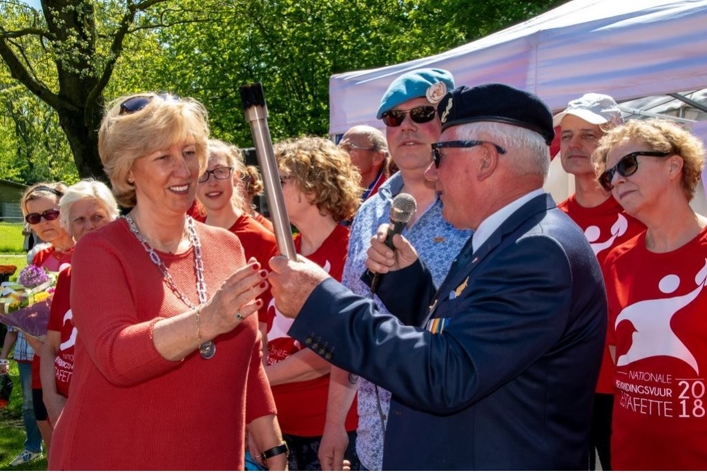 Burgemeester Driessen krijgt het bevrijdingsvuur uit handen van een veteraan.  Foto: Johan Kranenburg © uitgeverij Verhagen
