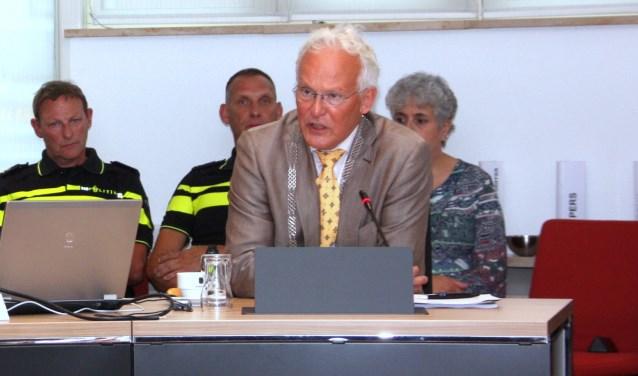 Burgemeester Rijpstra legt in de raadsvergadering  een verklaring af over de noodverordening. Links politiechef Henk Woppenkamp. | Foto: WS