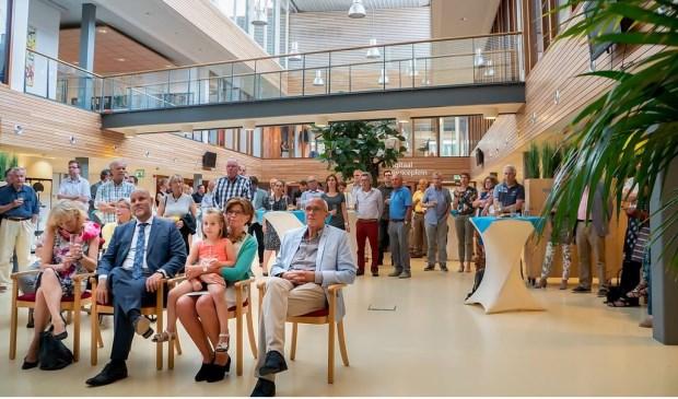 De oud-wethouders en hun echtgenoten - en kleinkind van Kees Wassenaar - luisteren naar de toespraak van burgemeester Driessen.