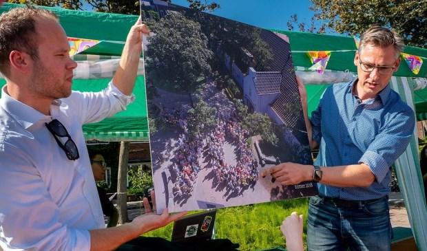 Interim schoolleider Freek van der Brugge (links) en de nieuwe directeur Maarten Meijers tonen de jubileumfoto.
