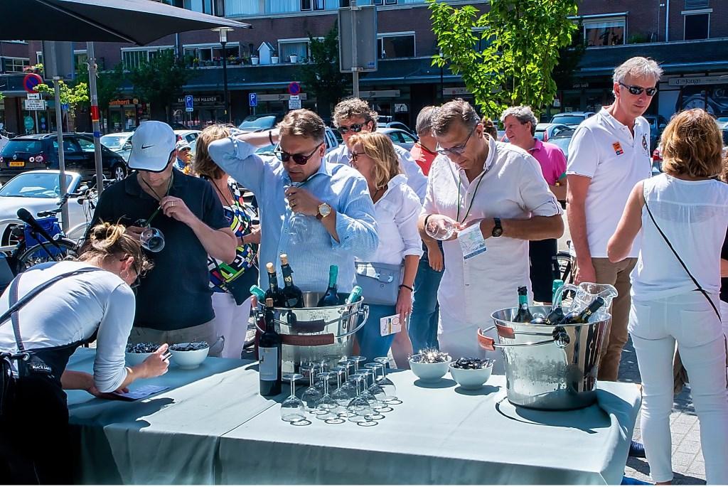 Deelnemers laten hun passe partout afstempelen en brengen hun glas in gereedheid bij IJscafé Danice.