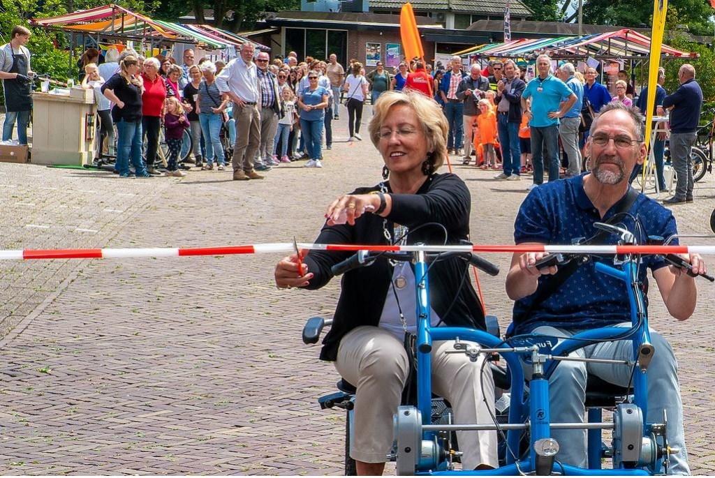 Burgemeester Laila Driessen opent de bewonersmarkt. Naast haar op de duofiets fietsmaatje Jan de Meij.