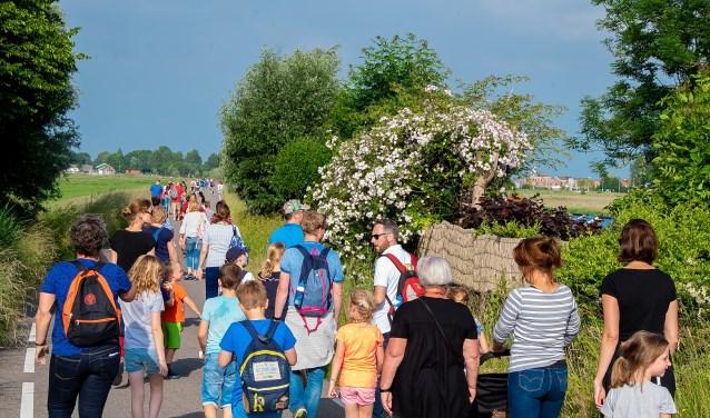 Lopers van de 5 kilometer op de fraaie Nieuweweg, die door de Boterhuispolder voert. | Foto: J.P. Kranenburg