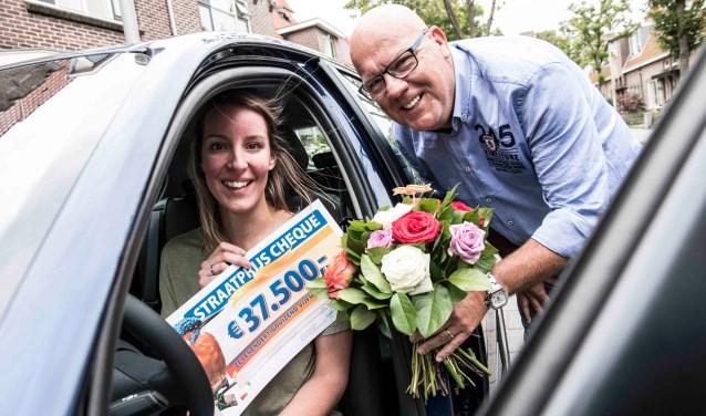 Liesbeth wordt verrast door Postcode Loterij-ambassadeur Gaston Starreveld met de PostcodeStraatprijs-cheque en de BMW. | Foto Jurgen Jacob Lodder