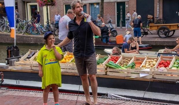 Plastic Soup Surfer Merijn Tinga als veilingmeester, met als hulpje een van de kinderen van Stichting Nadja.