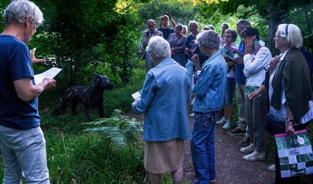 Jos Nijhof leest het gedicht 'Zoals' van Judith Herzberg voor bij het beeld 'Hond' van Patrick Visser.