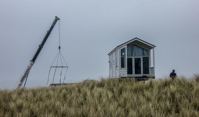 Een strandhuisje wordt tijdens de opbouw het strand opgereden.