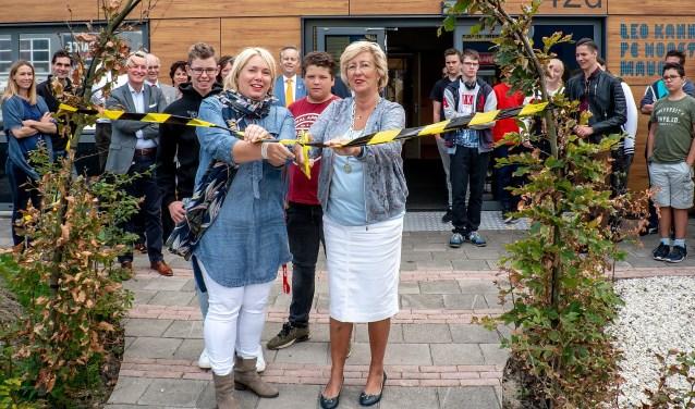 Burgemeester Laila Driessen en lerares Adinda Dernison openen het vergroende plein door een linkt in de beukenboog door te knippen. Net achter hen staan Stefan (links) en Danny, twee van de leerlingen die meegewerkt hebben aan het plan.