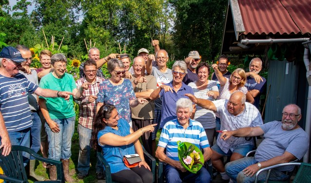 Zittend met de bloemen Gerard van Velzen, met om hem heen een aantal vrijwilligers van de schooltuinen.   Foto: J.P. Kranenburg