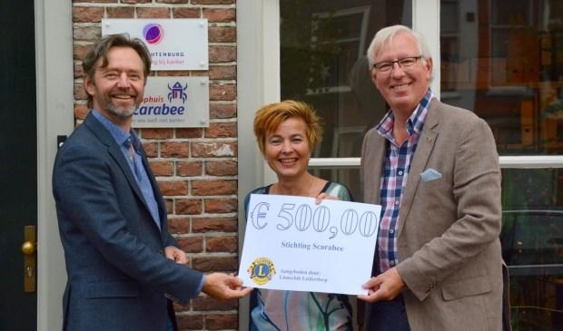 Brigitte van Elburg van Scarabee ontvangt de cheque uit handen van Lions Peter de Ligt (rechts op de foto) en Huibrecht Bos.
