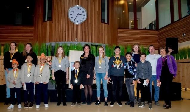 Alle Leiderdorpse toppers bij elkaar met in het midden wethouder Angelique Beekhuizen en rechts organisator Marijke Mening, de jongerenjury en de bestuursleden van Tamarco die het jongerenbestuur vertegenwoordigden.